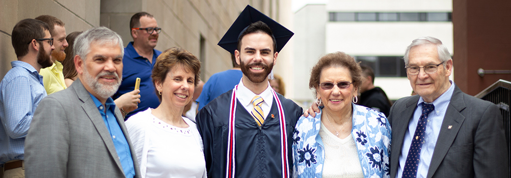Graduate pictured with his parents and grandparents at Commencement.