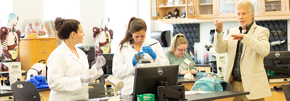 students earning a biology degree and their professor are in a biology labs wearing lab coats