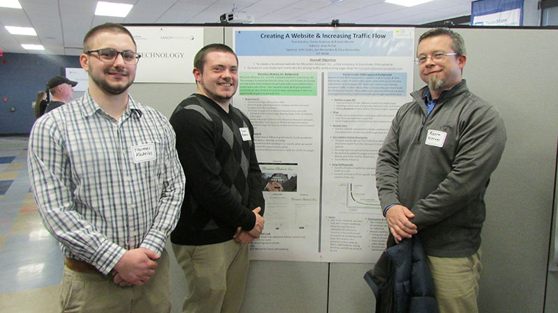 three students with research poster