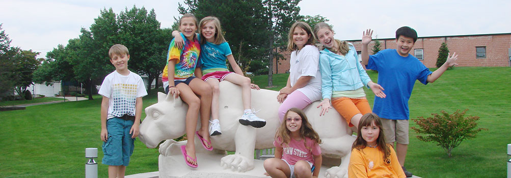 young students pose with Nittany Lion statue during Penn State Scranton summer camp