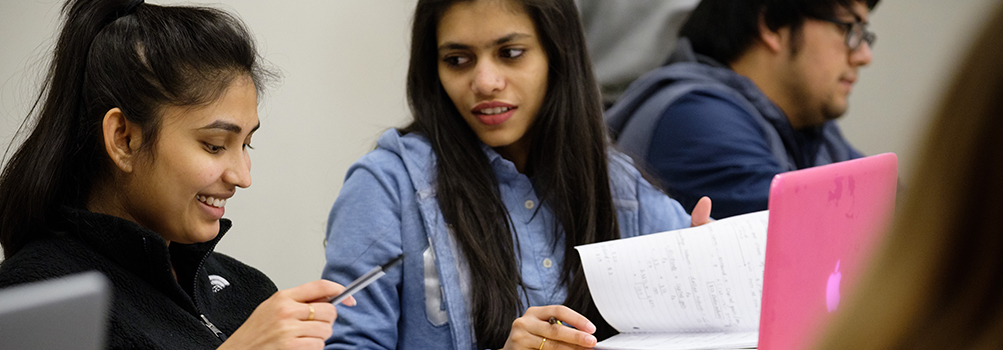 psychology degree seeking students in class reviewing notes together from a notebook