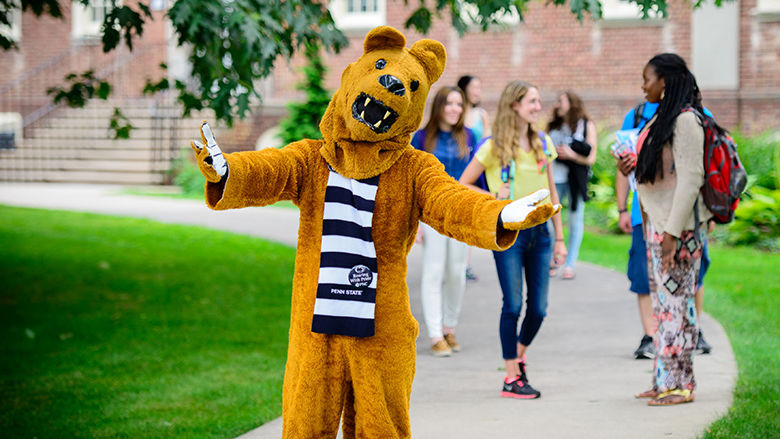 lion mascot on campus sidewalk, with arms stretched out in a welcoming way