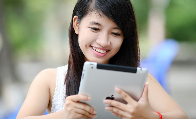 smiling girl looks at ipad