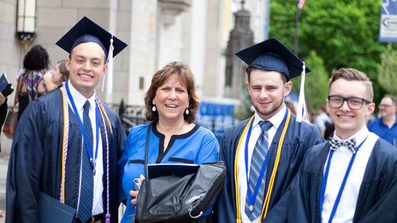 three graduates in cap and gowns pose with faculty member