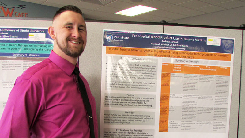 student standing next to poster of research project