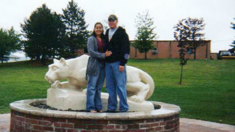 a young couple posing near nittany lion statue