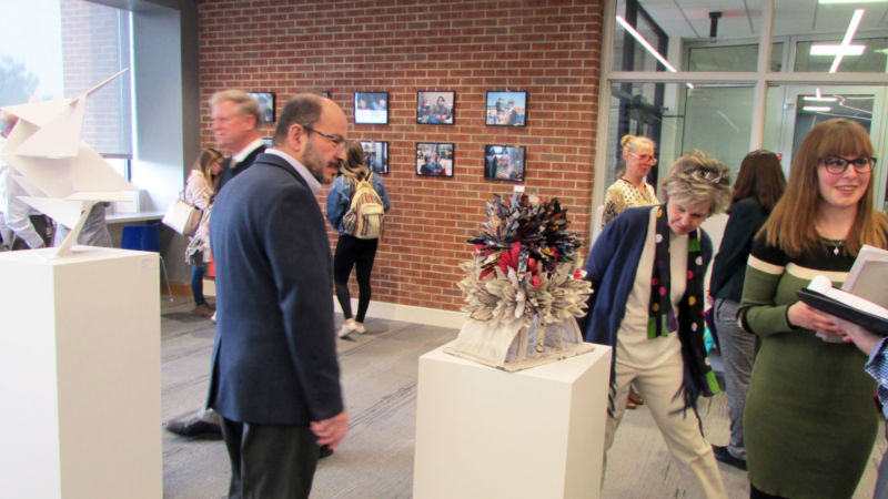 campus chancellor takes a closer look at one of the sculptures