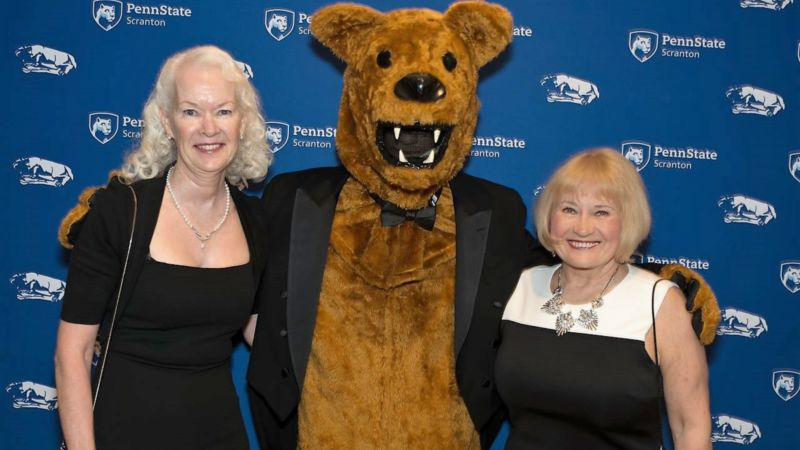 Former employees Margie and juliet pose with the Nittany Lion