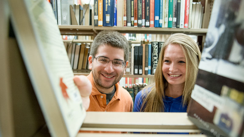 Two students check out books in the Penn State Scranton library.