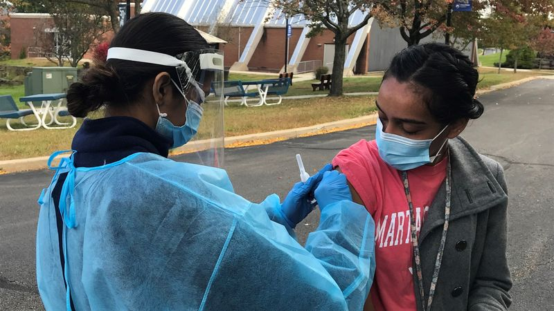 Campus nursing student prepares to give flu shot to student