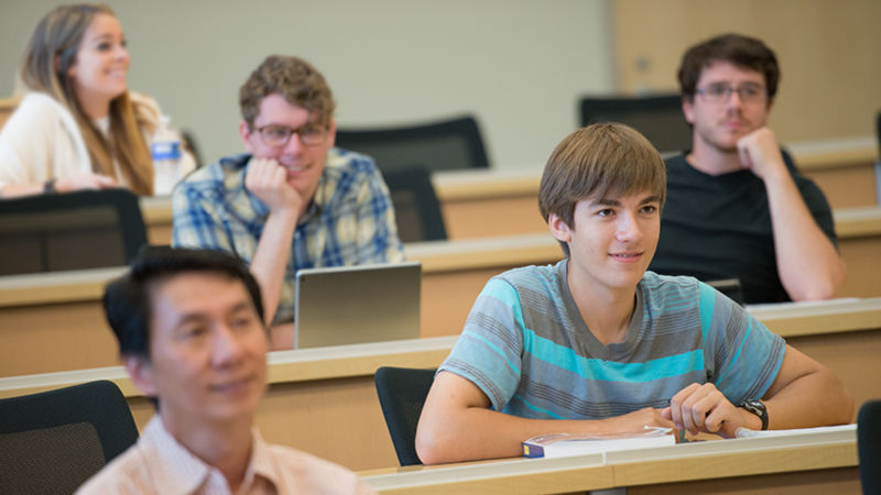 students in lecture classroom setting smile and while listening to presenter