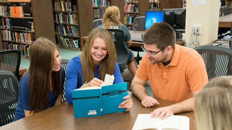 Three students share a textbook at a library table.