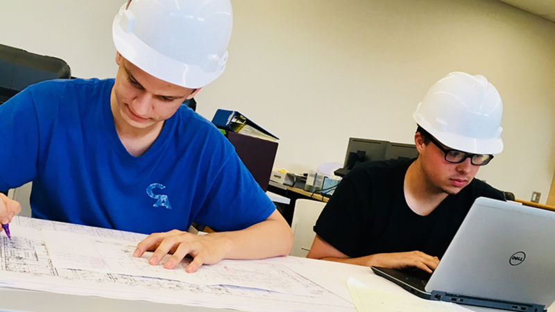 Students in hard hats working on construction plans