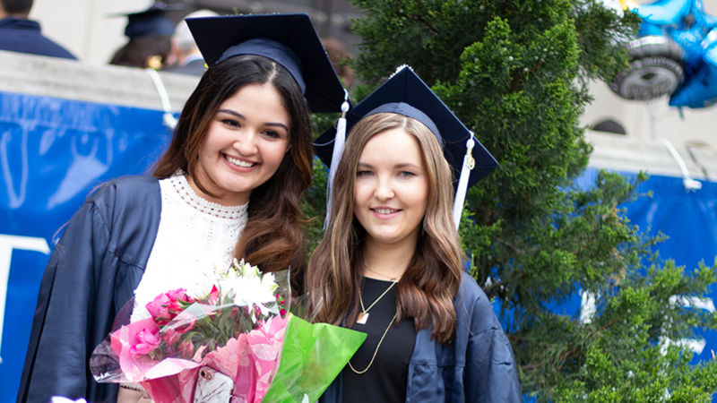 two girls at graduation wearing grad cap and gown holding flowers
