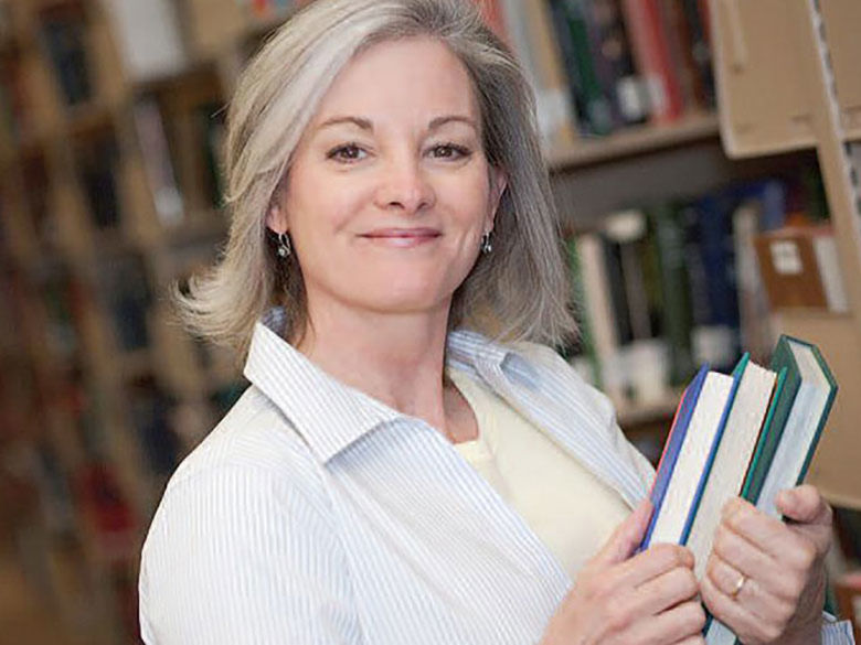 smiling professional with books in library