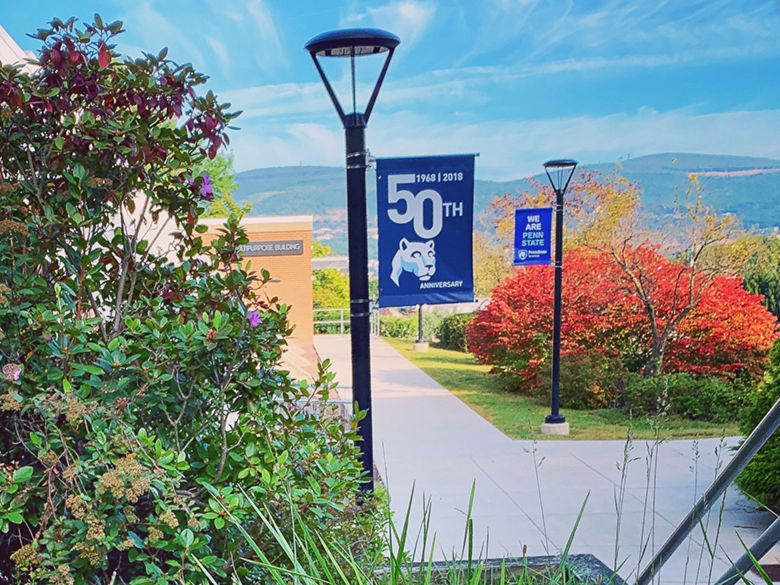 sidewalks and lamp posts with PSU flags, by the gym, overlooking the valley