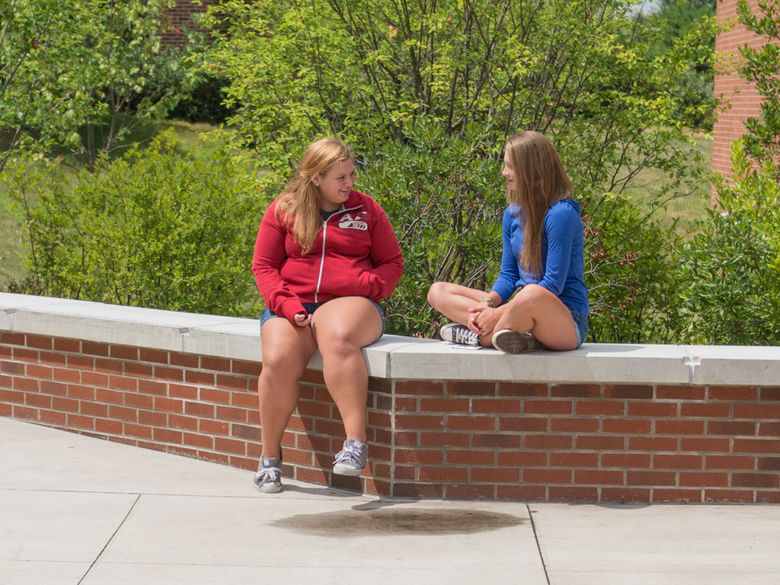 two high school students sit on a brick bench surrounded by trees
