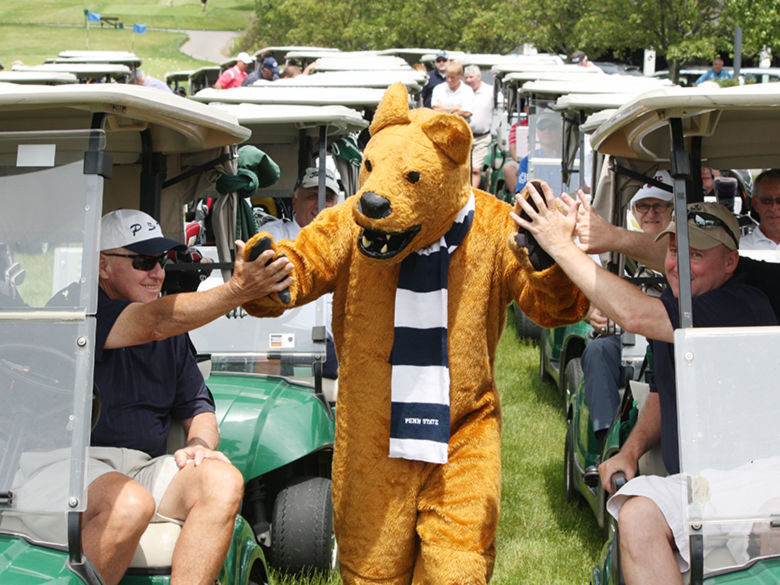 Lion mascot walking between two rows of golf carts driven by golfers