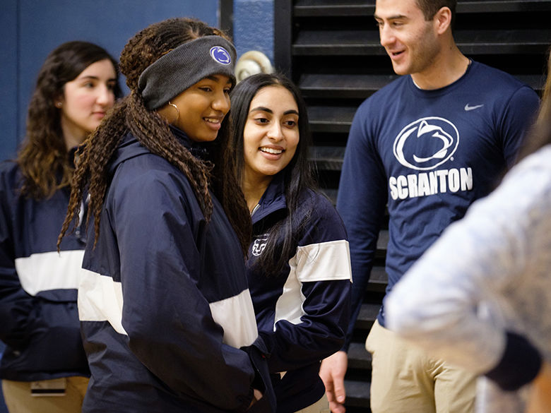 four students in Penn State attire speak with New Students