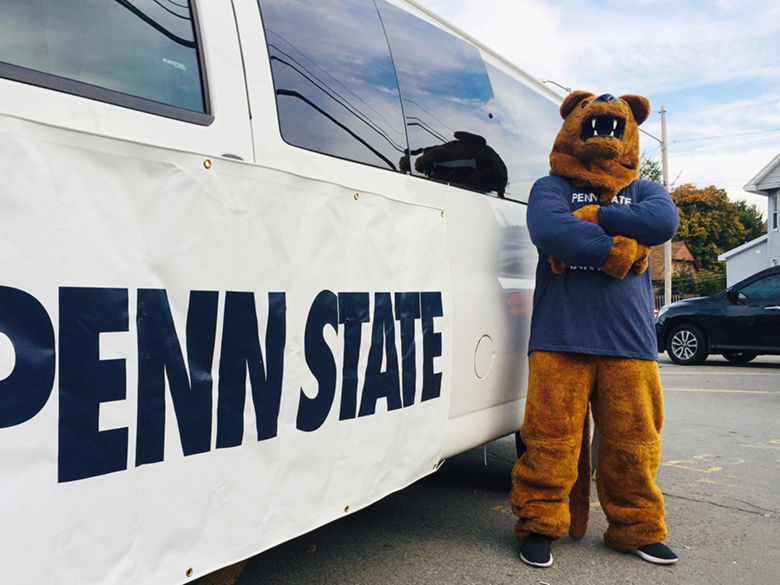 Lion mascot stands by vehicle marked Penn State