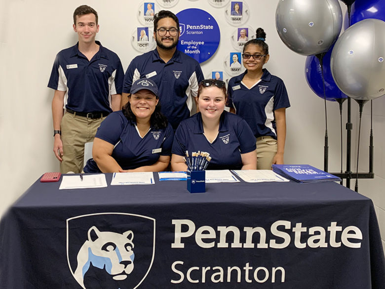 Five students pose behind a table that has a table cloth that reads Penn State Scranton