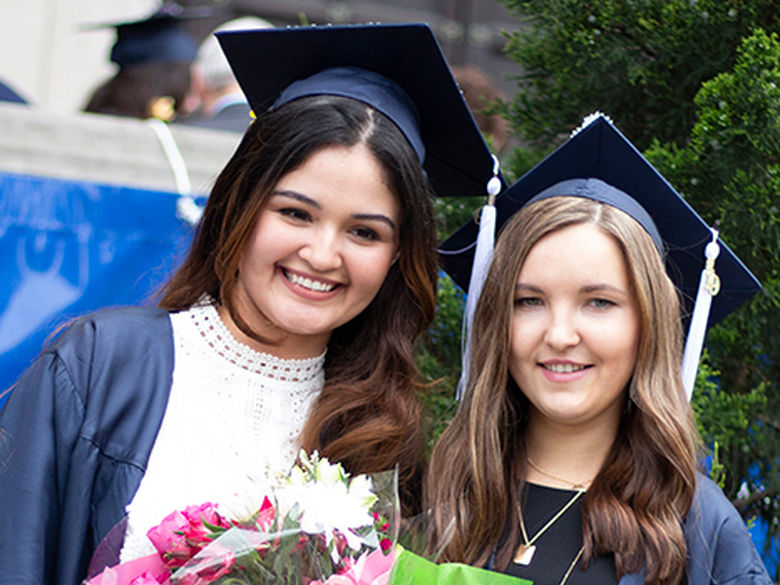 two smiling girls in graduation cap and gowns