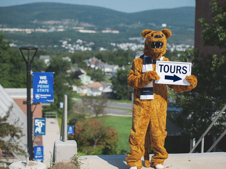 Nittany Lion Mascot holding sign that reads tour.