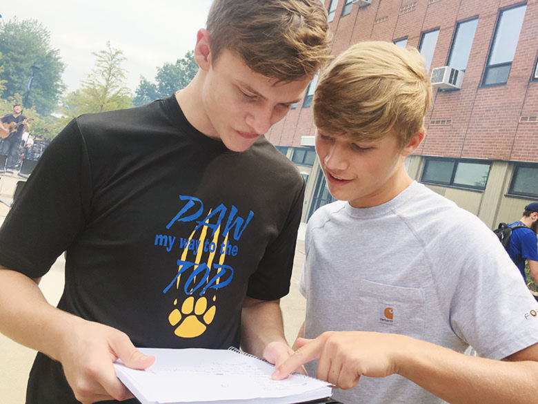 Two students looking at a note book and planning a visit