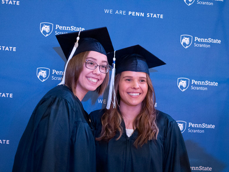 two students in caps and gowns pose in front of Penn State backdrop