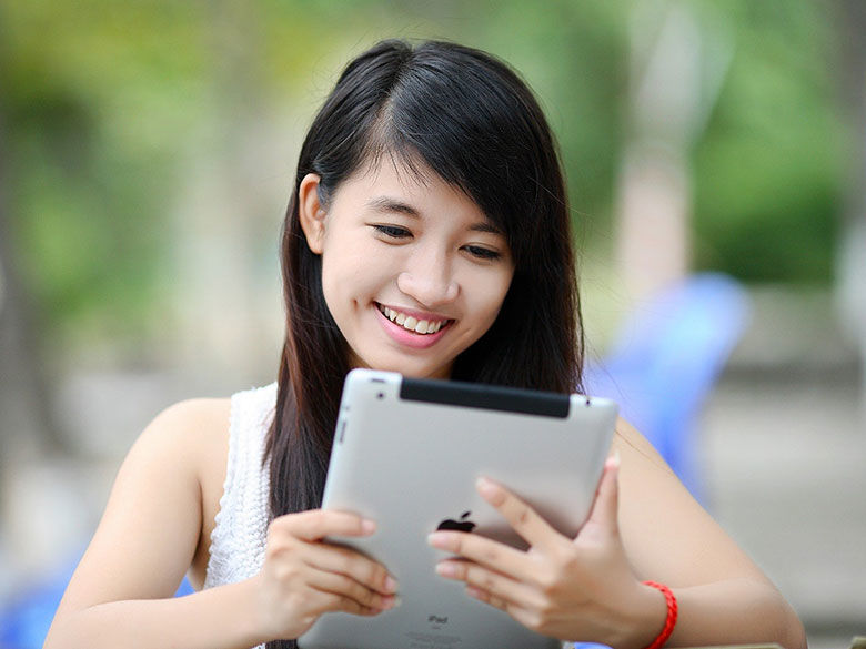 girl smiling while looking at her electronic tablet