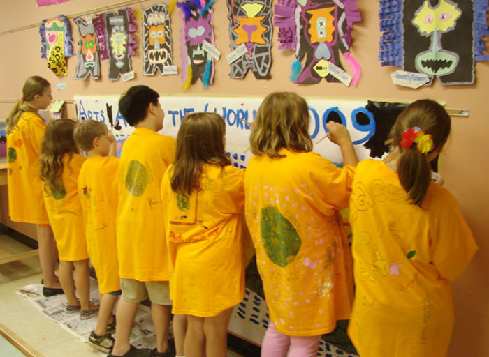 Students in matching yellow camp t-shirts paint a mural on a wall