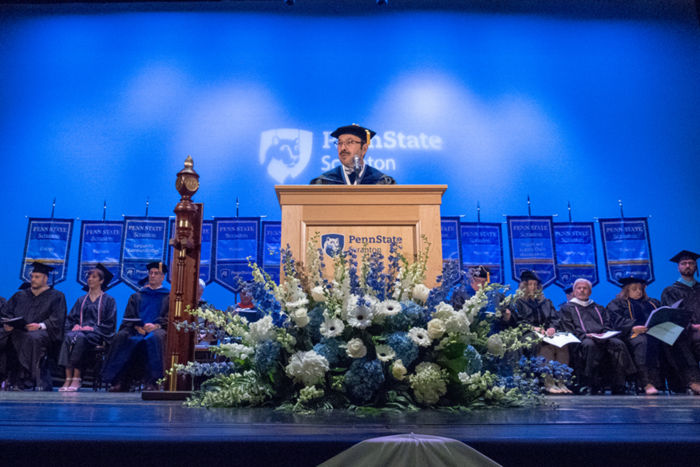 Man wearing graduation hat and robe on stage in front of a podium. Stage party, people  seated behind him.