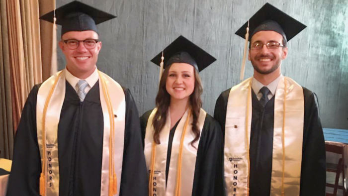 three students pictured wearing cap and gown and white honors sashes and yellow honors cords