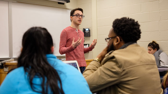 male student standing in front of classroom while peers listen to him speak
