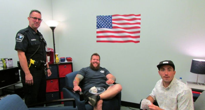 campus police office and two military students sit in comfortable veteran lounge