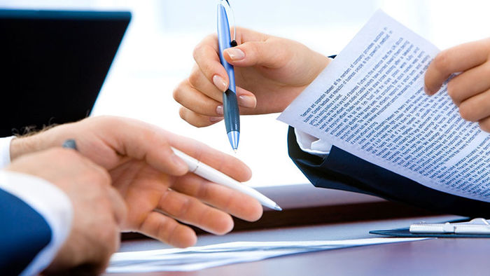 sets of hands of two people holding papers and pen review writing content
