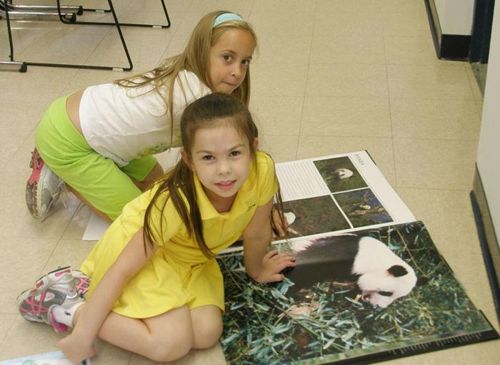 two girls look at images of panda bear