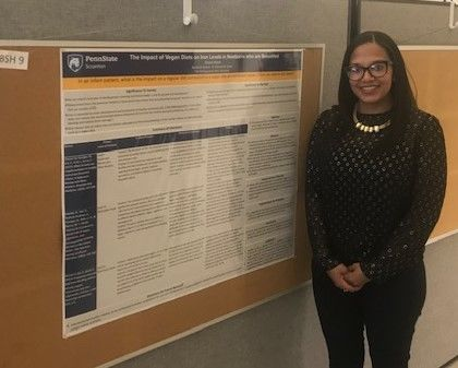 Student Brittany Hebron standing near her poster at the Penn State Eastern Regional Undergraduate Research Symposium at Penn State Hazleton, 2019
