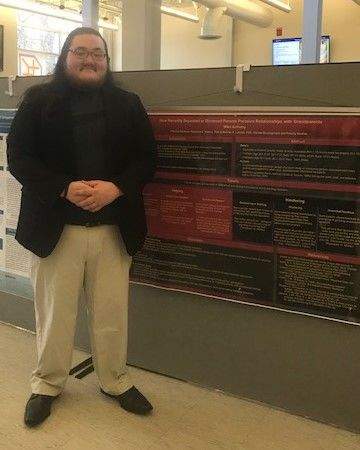 Student Michael Anthony standing near her poster at the Penn State Eastern Regional Undergraduate Research Symposium at Penn State Hazleton, 2019