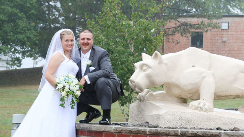 bride and groom pose near Nittany Lion statue
