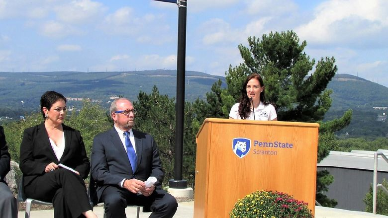 emily scarfo speaking at a podium at a campus event