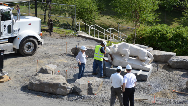 crews place lion at new site