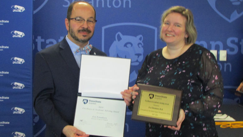 man in suit presents certificate to smiling woman