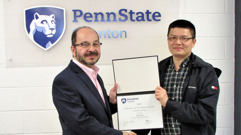 man in suit presents certificate to smiling man