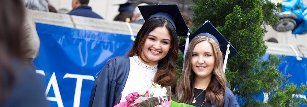 two smiling girls in caps and gowns holding diplomas